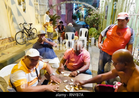 Cartagena Colombia Old Walled City Center centre Getsemani neighborhood night nightlife Hispanic resident residents man friends playing dominoes watch - Stock Image