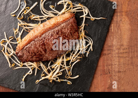 Kobe meat, wagyu beef steak, cooked, shot from the top with soy sprouts on a black slate plate, with a place for text - Stock Image