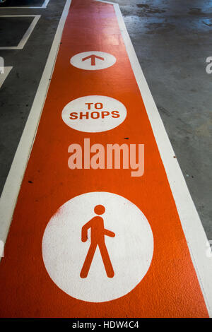 An orange painted pathway for pedestrians to shops - Stock Image