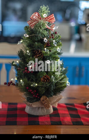 A minature tabletop Christmas tree with burlap on a red and black table runner. Indoor Christmas decor. - Stock Image
