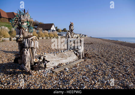 Driftwood figures on the beach at the western end of the seafront of Bexhill on Sea. Created by local artist Andy - Stock Image