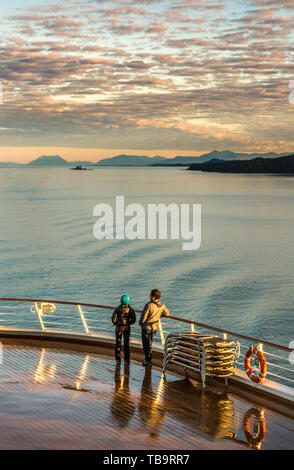 September 17, 2018 - Clarence Strait, AK: Warmly dressed couple, early morning light, viewing scenery off Lido Deck of The Volendam cruise ship. - Stock Image