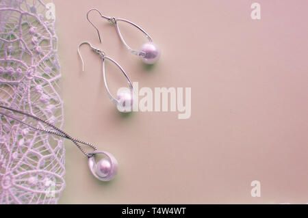 Beautiful silver shiny pearl jewelry, trendy glamorous earrings, chain on pink purple background with exquisite lace. Flat lay, top view, copy locatio - Stock Image