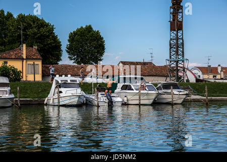 Boats moored at the dock with people preparing to sail in Caorle - Italy - Stock Image