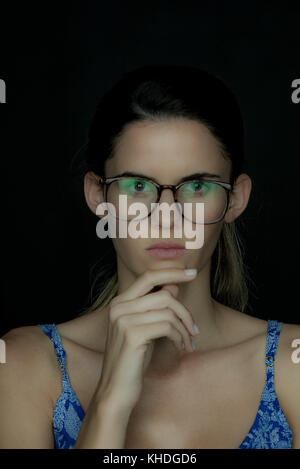 Young woman wearing glasses, deep in thought, portrait - Stock Image