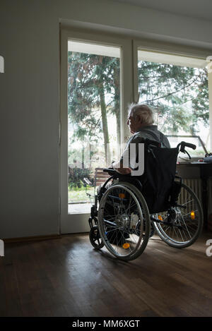 Senior man in wheelchair looking out by window - Stock Image