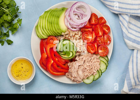 tuna salad, quinoa and vegetables: cucumber, avocado, peppers, cherry tomatoes, parsley on a white plate on a blue - Stock Image