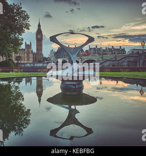 The Houses of Parliament reflected in a fountain pond across the River Thames - Stock Image