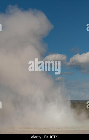 GeyserErupts with Large Spray in Yellowstone wilderness - Stock Image