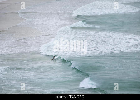 A lone surfer riding a wave at Crantock Beach in Newquay in Cornwall. - Stock Image