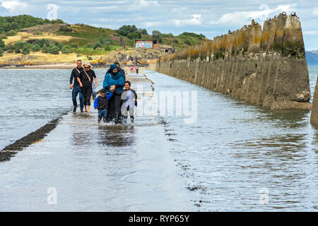 Incoming tide on the causeway, with 2nd World War anti-boat pylons, leading to Cramond Island, Cramond, Edinburgh, Scotland, UK - Stock Image