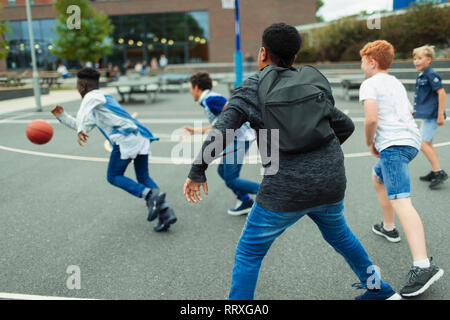 Junior high boy students playing basketball in schoolyard - Stock Image