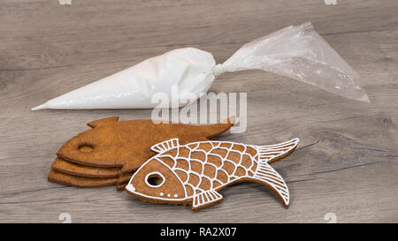 Christmas pastry and icing bag stacked on wood background. Close-up of traditional Xmas nad New Year gingerbreads in fish shape. Prepare to decorating. - Stock Image