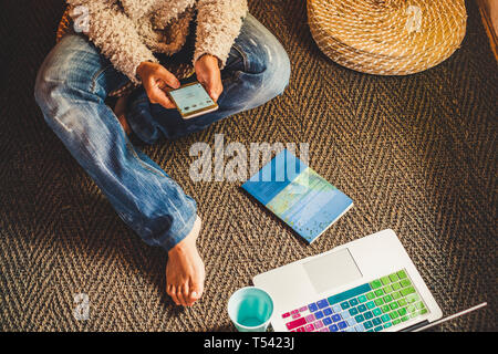 Technology and modern devices phone and laptop concept with woman using cellular and notebook on the floor at home - people internet social addicted o - Stock Image