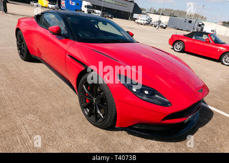 An red, Aston Martin DB11, parked in the International Paddock, during the 2019 Silverstone Classic Media Day - Stock Image