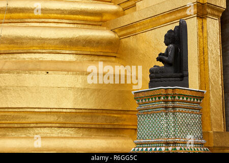 A small Buddha statue against a gilt column inside the Grand Palace in Bangkok, Thailand. - Stock Image