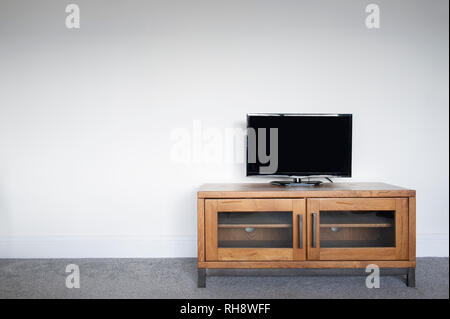 An industrial Wood and Metal TV Unit in a living room interior against a plain white wall. - Stock Image