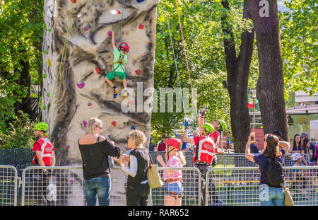 shot of little boy in a harness climbing a wall with grips outdoors - Stock Image