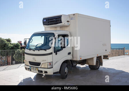 A Small Compact White Toyota Dyna Refrigerated Delivery Truck By The Ocean In Portugal - Stock Image