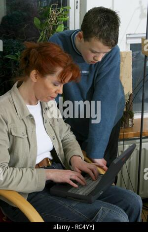 Mother using laptop in 2003 and curious son looking at screen. - Stock Image
