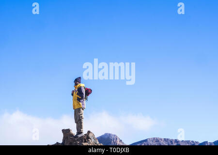 Hiker man standing and looking around at the top of the mountain with clear blue sky with clouds in backgorund - success and hiking outdoor concept -  - Stock Image