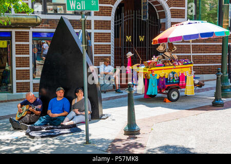 ASHEVILLE, NC, USA-24 JUNE 18: Musicians, and a cart vendor on a sunny day at the iconic flat iron, across from the flat iron building at Battery Park - Stock Image