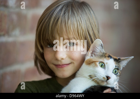 Portrait of a boy holding calico cat, outdoors. - Stock Image