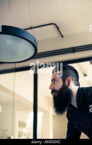 Man looking away in thought in office - Stock Image