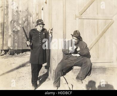Policeman sneaking up on man with stolen purse - Stock Image