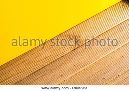 Wooden plank surface next to yellow barrier. - Stock Image