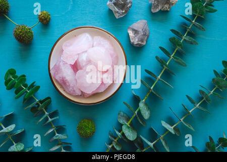 Rose Quartz with Quartz and Eucalyptus on Turquoise Table - Stock Image
