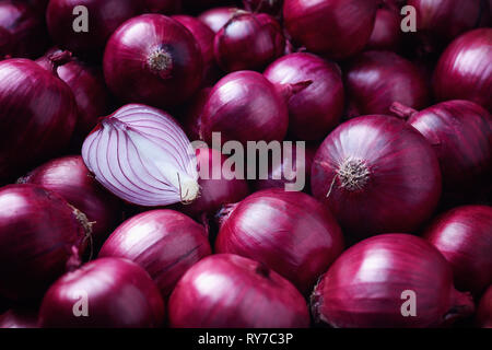 Full Frame Shot Of Purple Onions. Fresh whole purple onions and one sliced onion. - Stock Image