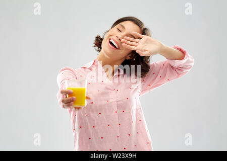 happy yawning young woman in pajama with juice - Stock Image