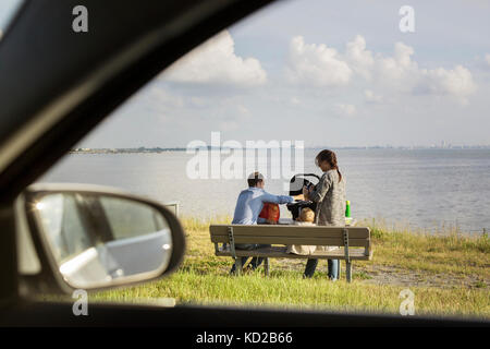 Parents with son (18-23 months) sitting on bench by sea - Stock Image