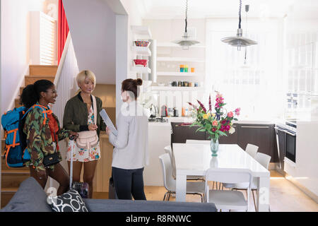 Real estate agent greeting young women friends arriving at house rental - Stock Image