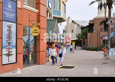 Mature and senior shoppers walking past stores in the resort of HarborWalk Village in Destin Florida, USA. - Stock Image