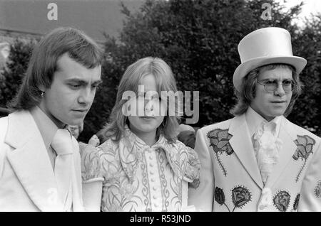 Elton John (right) pictured here as best man to his songwriting partner Bernie Taupin.  Bernie marries 19 year old American student Maxine Feibelman on Saturday 27th March 1971 at  Holy Rood Catholic Church, in Market Rasen, Lincolnshire.  Best man Elton wears a white suit embroided with red and yellow roses, and a white silk top hat. All made in Los Angeles, by the same tailer who has designed suits for Elvis Presley. (Tailer is named in captioned but writing difficult to make out)  Bride Maxine, wears a full length traditional gown in white with old gold irises embroided on the bodice.  Groo - Stock Image