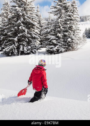 small girl walking in deep snow with sledge in hand and wooded winter  mountain landscape behind - Stock Image