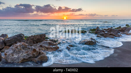 Sunset over the rocky shore of the Gulf of Mexico at Caspersen Beach in Venice Florida - Stock Image