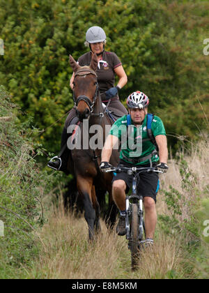 Man on a mountain bike with woman on a horse along a bridleway, Chettle, Dorset, UK - Stock Image