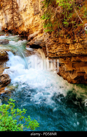 Rushing waterfall flows into the turquoise colored Johnston Canyon creek at Banff National Park in Alberta, Canada. The waters empty into the Bow Rive - Stock Image