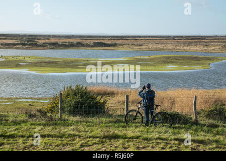 RSPB Medmerry Nature Reserve by the coast, West Sussex, UK. Birdwatcher on a bicycle looking at birds on the stilt pools through binoculars - Stock Image