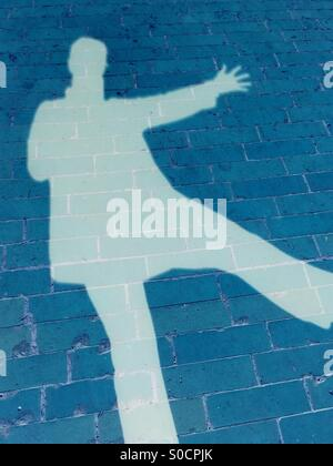 Silhouette selfie of person with arm and leg extended, pretending to fall on one foot. Turquoise shadow on cerulean - Stock Image