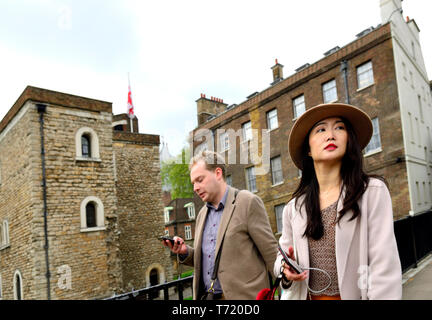London, England, UK. Japanese tourist and man on his mobile phone, College Green, Westminster - Stock Image