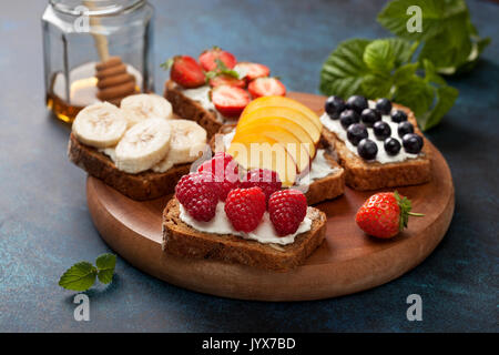 Diet breakfast. Toasts with cream cheese and fresh berries and fruits: banana, raspberry, blueberry, strawberry, peach. - Stock Image