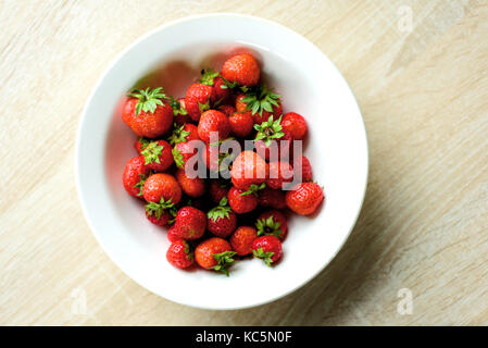 White ceramic kitchen bowl full of red strawberries taken from an aerial overhead position with domestic counter - Stock Image