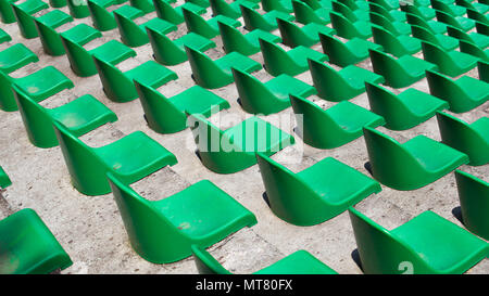 Many green plastic seats in rows in an empty stadium. - Stock Image