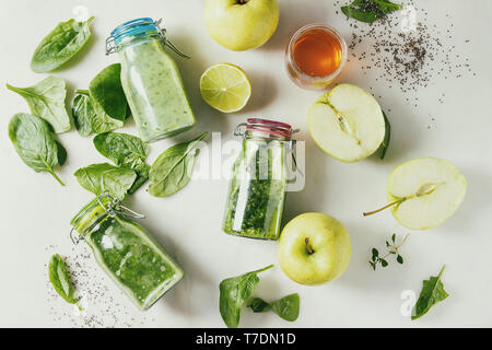 Variaty of green spinach kale apple honey smoothies in glass bottles with ingredients above over white marble background. Healthy organic eating. Flat - Stock Image