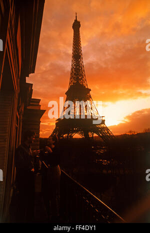 Couple on apartment balcony enjoying sunset drink under dramatic sky near Eiffel Tower in Paris - Stock Image