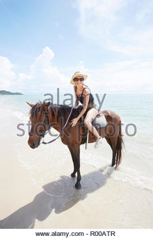 Young woman riding horse on beach - Stock Image